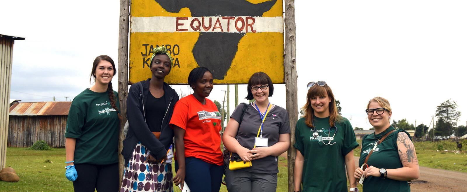 Projects Abroad medical volunteers pose next to an 'Equator' sign in Nanyuki, Kenya
